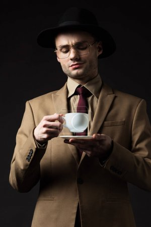 Photo for Elegant man in beige suit, hat and eyeglasses holding coffee cup and saucer isolated on black - Royalty Free Image
