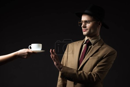Photo for Elegant man in beige suit, hat and eyeglasses refusing coffee from waiter isolated on black - Royalty Free Image