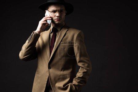 Photo pour Homme élégant sérieux en costume beige, chapeau et lunettes parler sur smartphone isolé sur noir - image libre de droit