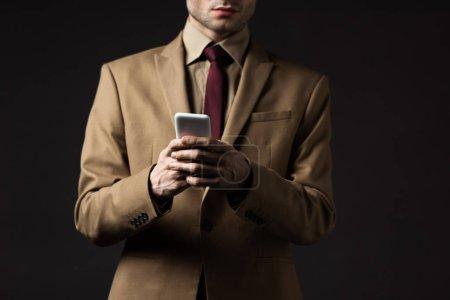 recortado vista de hombre elegante serio en traje beige usando teléfono inteligente aislado en negro
