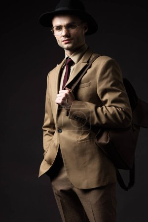 serious elegant man in beige suit, hat and eyeglasses holding brown leather backpack isolated on black