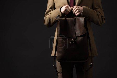 Photo pour Vue recadrée de l'homme élégant en costume beige tenant sac à dos en cuir brun isolé sur noir - image libre de droit
