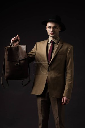 elegant man in beige suit, hat and eyeglasses holding brown leather backpack isolated on black