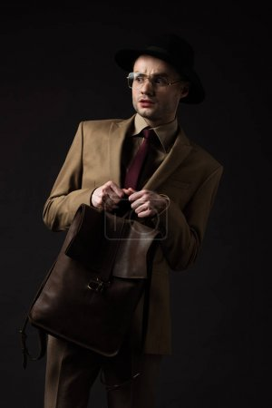 Photo for Worried elegant man in beige suit, hat and eyeglasses holding brown leather backpack isolated on black - Royalty Free Image