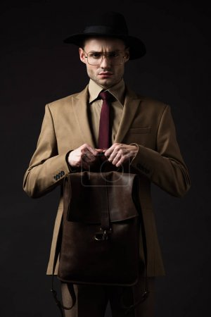 Photo for Tense elegant man in beige suit, hat and eyeglasses holding brown leather backpack isolated on black - Royalty Free Image