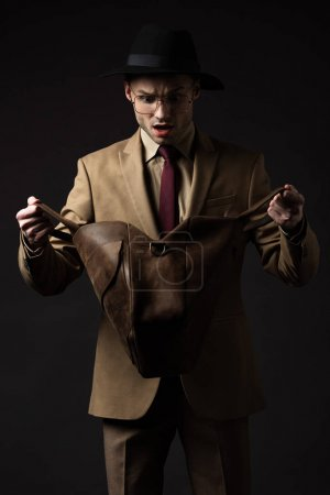 Photo for Shocked elegant man in beige suit, hat and eyeglasses looking in brown leather bag isolated on black - Royalty Free Image