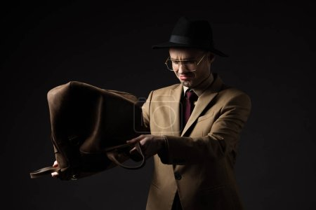 sad elegant man in beige suit, hat and eyeglasses shaking out brown leather bag isolated on black