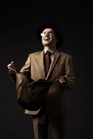 happy elegant man in beige suit, hat and eyeglasses holding brown leather bag isolated on black
