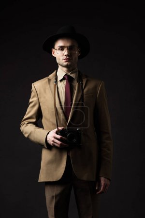 Photo for Elegant man in beige suit, hat and eyeglasses with film camera isolated on black - Royalty Free Image