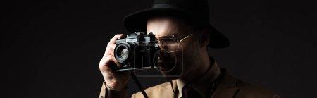 Photo pour Élégant homme en costume beige, chapeau et lunettes prenant des photos sur la caméra du film isolé sur noir, panoramique - image libre de droit