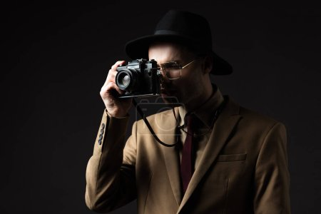 Photo for Elegant man in beige suit, hat and eyeglasses taking picture on film camera isolated on black - Royalty Free Image