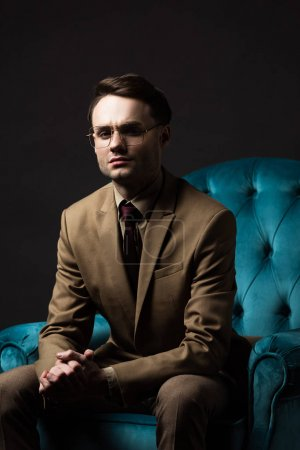 Photo for Elegant man in beige suit eyeglasses sitting with clenched hands in blue velour armchair isolated on black - Royalty Free Image