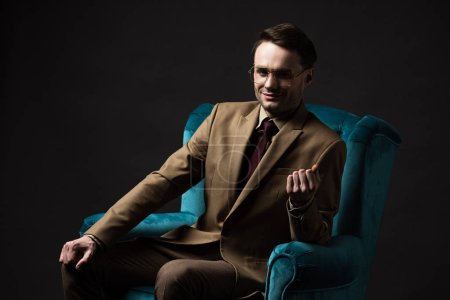Photo for Smiling elegant man in beige suit eyeglasses sitting in blue velour armchair isolated on black - Royalty Free Image