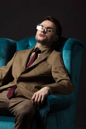 Photo for Elegant man in beige suit eyeglasses sitting in blue velour armchair isolated on black - Royalty Free Image
