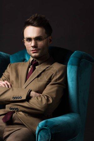 Photo pour Homme élégant en costume beige lunettes assises en velours bleu fauteuil avec bras croisés isolés sur noir - image libre de droit