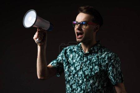 Photo pour Homme à la mode aux lunettes en chemise de couleur bleue criant dans un haut-parleur isolé sur noir - image libre de droit