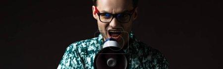 Photo pour Homme à la mode dans les lunettes de vue en chemise colorée bleue criant dans haut-parleur isolé sur noir, plan panoramique - image libre de droit