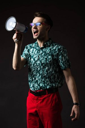 Photo for Fashionable man in eyeglasses in blue colorful shirt and red pants shouting in loudspeaker isolated on black - Royalty Free Image
