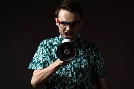 Photo pour Homme à la mode dans les lunettes en chemise colorée bleue criant dans haut-parleur isolé sur noir - image libre de droit