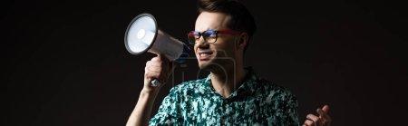 Photo pour Homme à la mode aux lunettes en chemise de couleur bleue criant dans un haut-parleur isolé sur une photo panoramique noire - image libre de droit