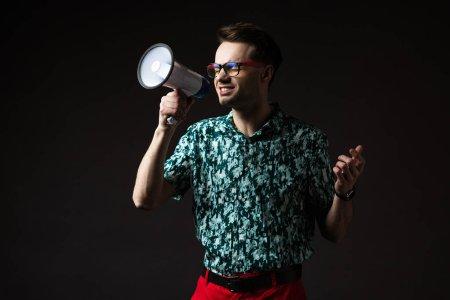 Photo pour Homme à la mode dans les lunettes en chemise colorée bleue et pantalon rouge criant dans haut-parleur isolé sur noir - image libre de droit