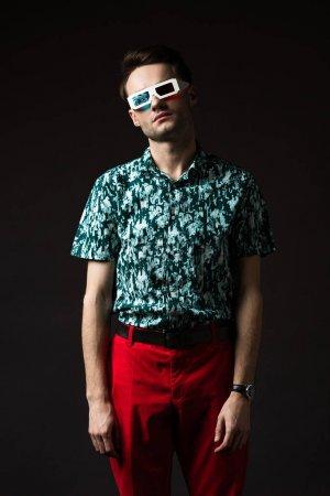 Photo pour Homme à la mode dans des lunettes 3d en chemise bleu coloré et pantalon rouge isolé sur noir - image libre de droit