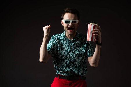 excited fashionable man in 3d glasses in blue colorful shirt and red pants holding popcorn and showing yeah gesture isolated on black