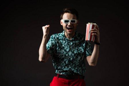 aufgeregter modischer Mann mit 3D-Brille in blauem buntem Hemd und roter Hose, Popcorn in der Hand und Yah-Geste isoliert auf schwarz