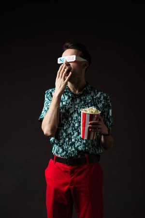 fashionable man in 3d glasses with open mouth in blue colorful shirt and red pants holding popcorn isolated on black