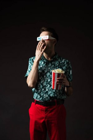 Photo for Fashionable man in 3d glasses with open mouth in blue colorful shirt and red pants holding popcorn isolated on black - Royalty Free Image