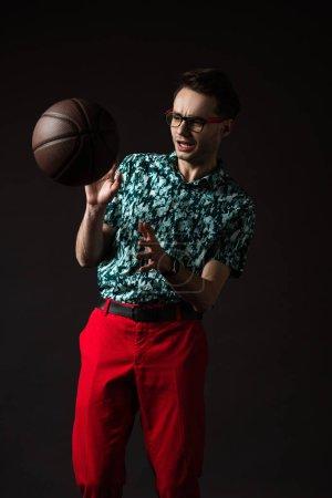 Photo pour Homme à la mode effrayé dans des lunettes en chemise colorée bleue et pantalon rouge avec basket isolé sur noir - image libre de droit