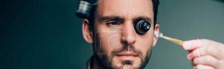 Enfoque selectivo del relojero en lupa de gafas que sostiene la parte del reloj, tiro panorámico