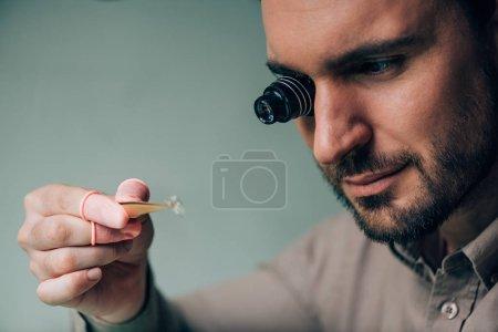 Photo pour Belle horlogère en loupe de lunettes tenant pièce de montre isolée sur gris - image libre de droit
