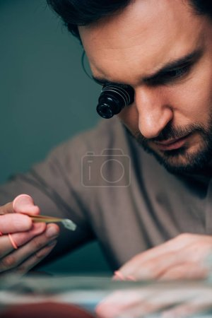 Selective focus of handsome clockmaker working with watch part at table