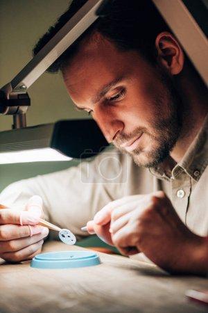 Photo pour Vue latérale de l'horloger utilisant le ventilateur pour nettoyer la partie de montre à la table - image libre de droit