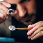Selective focus of watchmaker holding eyeglass lou...