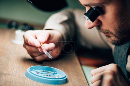 Photo for Side view of watchmaker holding watch part by tool tray on table - Royalty Free Image