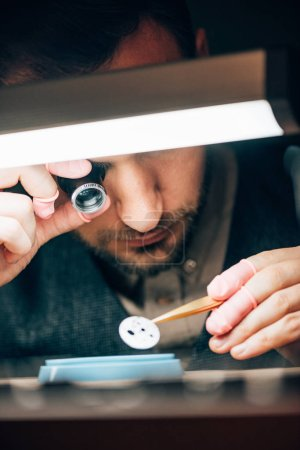 Photo for Selective focus of watchmaker holding eyeglass loupe and watch part at working table - Royalty Free Image