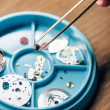Cropped view of watchmaker holding watchpart in tw...