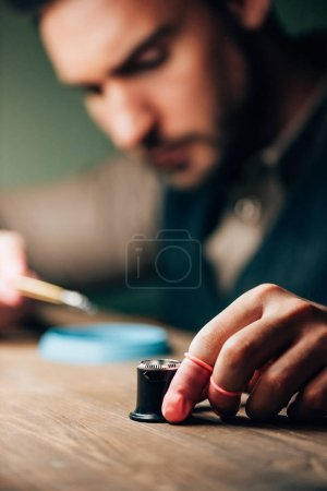 Selective focus of watchmaker holding eyeglass loupe while working at table