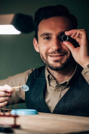 Smiling watchmaker with eyeglass loupe holding watch part while holding at camera