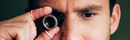 Photo for Cropped view of watchmaker in latex fingertips holding eyeglass loupe isolated on green, panoramic view - Royalty Free Image