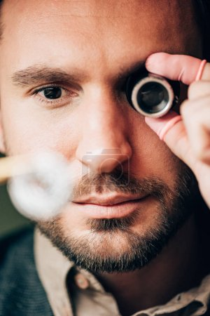 Selective focus of handsome watchmaker holding eyeglass loupe and watch part