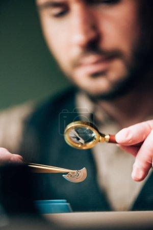 Photo pour Focus sélectif de l'horloger travaillant avec une pièce de montre dans une pince à épiler et une loupe à table - image libre de droit