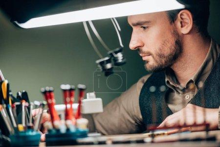 Photo pour Concentration sélective du beau horloger travaillant avec des équipements à table - image libre de droit