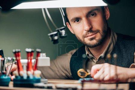 Photo pour Beau horloger regardant la caméra tout en travaillant avec des pièces de montres et une loupe - image libre de droit