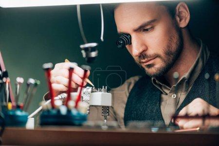 Photo pour Focus sélectif de l'horloger réparer montre-bracelet à la table - image libre de droit