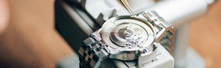 Photo pour Vue panoramique de la montre-bracelet sur testeur de montre par pince à épiler sur la table - image libre de droit
