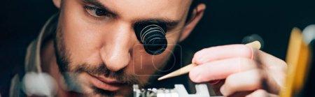 Photo pour Plan panoramique de l'horloger en loupe de lunettes travaillant avec une montre-bracelet isolée sur noir - image libre de droit