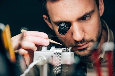 Photo pour Focus sélectif de l'horloger travaillant avec montre-bracelet sur chronographe porte-mouvement isolé sur noir - image libre de droit
